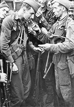 """US Ranger Sgt Alex Szima accepting a light for his cigarette apparently from a Sgt A. """"Bunny"""" Austin. The tall man behind is Cpl William Brady. Also in the photo but partially hidden is Staff Sgt Kenneth Stempson. Alex Szima died on 13th September 2006. Certainly Szima who was from Florida , Brady who was from Texas, and Stempson from Minnesota, were all in the 1st Battallion of the US Rangers with No.4 Commando at Dieppe. Austin may have been a war correspondent."""