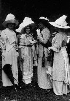 high society women at the royal ascot wearing long silk gloves, parasols, large decorated hats, daytime dress with dust coats to protect them from dust when driving in an automobile.