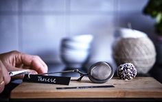 Quick tips for a perfect holiday bash: A close-up of someone tying a name tag onto an IKEA IDEALISK tea infuser.