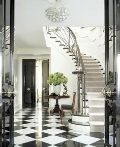 Grand entrance with black and white harlequin tile floors. Foyer stairway black doors center door knob checkerboard marble