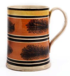 Mug. Creamware with slip banding, mocha decoration in dark brown, and turned reeding to the rim highlighted in yellow glaze.  Probably North Staffordshire, c. 1800. Height 141mm.