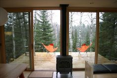 Sweet view with those orange chairs and the forest behind. mcglasson weehouse-4 from Tiny House Swoon. Click through for more pix.