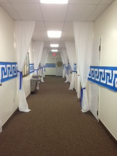 Classroom Hallway - Hung white tablecloths from ceiling and draped back with blue crepe paper / On long white strips of paper, we painted the greek pattern and then taped on walls