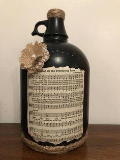 With sheet Hymn music. Painted Glass Bottles, Glass Jug, Bottles And Jars, Wine Jug Crafts, Mason Jar Crafts, Mason Jars, Recycled Wine Bottles, Wine Bottle Corks, Bottle Display