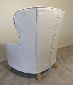 The back of this slipcover closes with a concealed zipper. On top is a linen flap with button tabs.