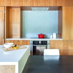 Kitchen, Wood Cabinet, Wall Oven, Cooktops, Recessed Lighting, Glass Tile Backsplashe, and Refrigerator The stools are from Crate & Barrel. The Hobsons chose a geometric-patterned glass tile backsplash by Island Stone. Induction cooktop and oven are by Bosch.