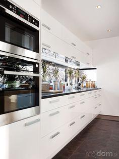 Pracovnú plochu v kuchyni efektne osvetľuje úzke pásové okno. Kombinácia bielych a tmavých plôch osvetlených prirodzeným svetlom pôsobí elegantne a zároveň príjemne.