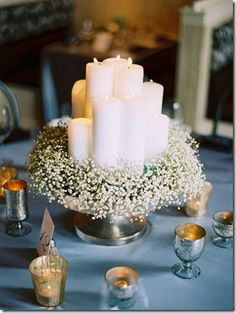 simple and elegant baby's breath with candles... you can dip your candles in melted crayon wax to color them if you want.  And downsize this look with votives inside glass bowls, with baby's breath around the candle inside, and a round white paper doily underneath.  Done it... it's a pretty inexpensive filler for rectangular table arrangements and the gaps in between major centerpieces.