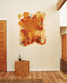 Walking in the front door it's hard to miss the square chunk of compressed-straw paneling—a building material-cum-sculpture that allows visitors to see what the house is made from. Kahn's paintings hang throughout the house, and several of the rugs are her original designs.  Photo by: Dave Lauridsen