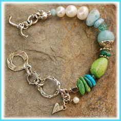 A bird watches over the Sea  from his seaside sanctuary...  Handcrafted sterling silver,  large Freshwater Pearls, Amazonite, Larimar,  Apatite, Primavera Stone, Sleeping Beauty Turquoise and Gaspeite  all representing shades of the sea.    Bracelet measures slightly over 7.5 inches  fits a wrist size 6.5 perfect.
