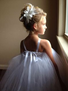 First Communion hairstyles girl updo with artificial flower