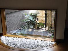 玄関正面の坪庭を望む地窓を砂利で演出