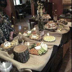 Our Engagement Party spread, wood slices as plate holders, burlap as a table cloth, tall vases full of yellow wildflowers and candles everywhere. Incredible!