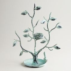 The lovely leaves and boughs of this handcrafted Green Tall Tree and Nest Jewelry Stand has punched holes that make it perfect for hanging your favorite earrings. With a charming bird perched on the bowl-like nest at the bottom, it's a unique way to store rings and other small trinkets, at an affordable price!
