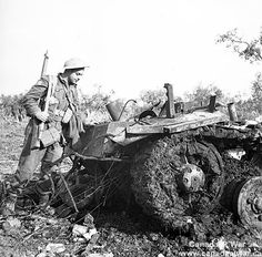 The Moro Valley - Private G.C. Butcher, 48th Highlanders of Canada, examines the wreckage of a German PzKpfW III tank destroyed by the Calgary Regiment.