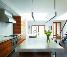 This kitchen's book-matched wood grain, Carrera marble– topped island and thin suspension lights elongate the space.