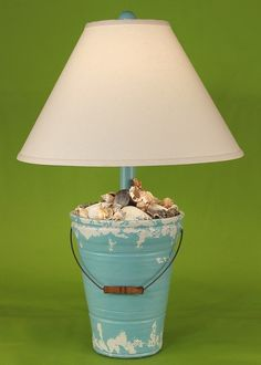 Hand-painted with a distressed shabby-chic teal green coastal finish, this beach bucket lamp is full of real gathered beach shells.