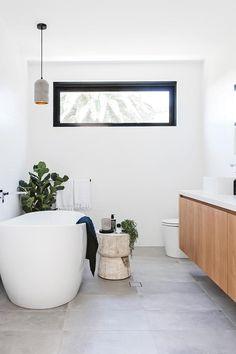 The high windows provide natural light while maintaining privacy. Cabinetry in American oak veneer contrasts with sleek concrete-look tiles bathroom ideas bathroom decor bathroom interior bathroom design badkamer ideeen bad Modern Bathroom Design, Bathroom Interior Design, Bathroom Styling, Modern White Bathroom, White Bathroom Tiles, White Bathrooms, Mosaic Bathroom, Light Bathroom, Glass Bathroom