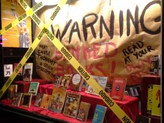 "Getting a head start on Banned Book Week in our display at Annie Bloom's Books. The smaller warnings read ""May cause thought and other discomforts"" and ""Read at your own risk!"""