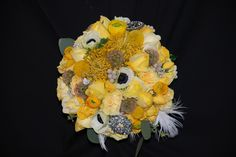 Summer bouquet of yellows and whites with tropical protea, brooches and ostrich feathers.
