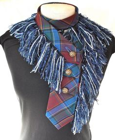 This blue,red and black plaid necktie is edged with salvaged blue colored fringe. The collar wraps around the neck twice and is secured with your