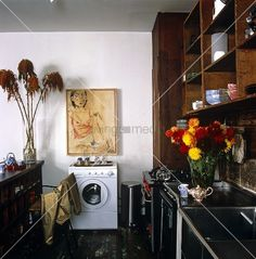 A self-portrait by artist Anh Duong hangs above the washing machine in her kitchen