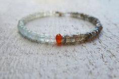 Mystic labradorite and aquamarine bracelet. A carnelian rondelle in the middle divides and gives a pop of color to this piece. Labradorite is a grey