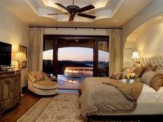 Long curtains pull back to reveal a beautiful view of the backyard swimming pool and outdoor fireplace. A velvet chair faces the plush, layered bed coverings and tufted headboard in this luxurious bedroom. A tray ceiling adds a final touch of style to the design.