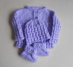 Want to make the perfect baby shower gift? This Lilac Blossom Baby Set will make any new mom giddy with excitement. The adorable free knitting patterns for babies included in this set are for a sweater, knit hat, and knit baby booties, keeping your b Knitting For Charity, Knitting For Kids, Free Knitting, Knitting Projects, Baby Set, Baby Baby, Baby Patterns, Knit Patterns, Baby Knitting Patterns Free Cardigan