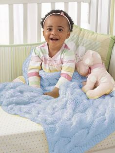 Follow the free knit pattern to create a cable baby blanket using Bernat Baby's Breath yarn.