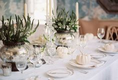 14 Gorgeous Holiday Table Settings - We love this gorgeous all-white tablescape with touches of green and silver. Great idea to set a sophisticated holiday table!