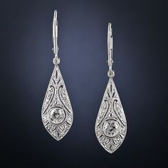 These delicate Art Deco diamond drop earrings are in such pristine condition that we are assuming they are later reproductions of their 1920s vintage counterparts. However, all of the diamonds: the two main European-cuts and the small rose-cuts and single-cuts all appear to be old. Whatever may be the case, these are truly exquisite and very wearable earrings. 7/8 inch-long, the leverbacks are new.