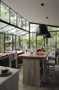 cuisine - kitchen - serre - greenhouse - veranda - conservatory - bois brut - table - tabouret - ilot - stool - island - ceiling light - plafonnier