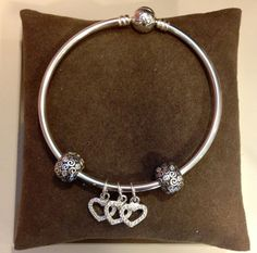 PANDORA Bangle with Pretty Clips and Three Heart Dangle Charms.