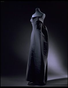 """Evening Dress, Paris, France, Cristóbal Balenciaga (born 1895 - died 1972): 1965-1966, Poult. """"Dresses in the Empire or Josephine style had a high waist-line under the bust. Balenciaga kept faith with this style, which was one of his favourites. The result was a number of outstanding designs, including the 'Amphora' dress shown here. Clever cutting and the use of a crisp silk created the cocoon-like back of the dress. Balenciaga finished the back with an enormous knotted sash. This…"""