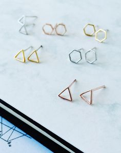 Create some symmetry with these dainty little geometric studs. Choose from a triangle or a hexagon in silver, gold or rose gold plate with Sterling...