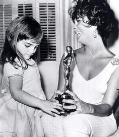 """Mom, can I borrow your Oscar?"""" Three-Year-old Liza Todd admires the Best Actress Oscar for ""BUtterfield 8"". 1960"