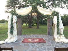 The gazebo will be draped with ivory fabric with a garland of bay laurel and clusters of seasonal greenery, white hydrangea, white stock, and ivory spray roses at the corners and at the top