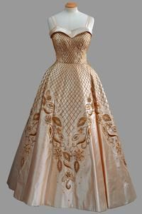 Cream silk gown with straps and full skirt with lattice and foliate beaded embroidery. Worn for official portraits of The Queen taken by Baron in 1957.