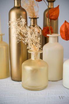 Champagne antique gold and bronze shimmer bottle vases, pop of orange. Elegant fall wedding decor.