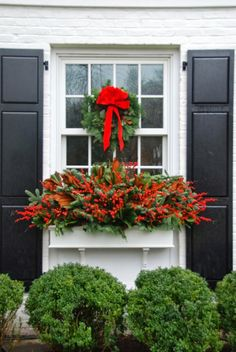 Red berries, magnolia leaves, and fir boughs in a window box, plus a green wreath with red ribbon...traditional, classic, and I love it.