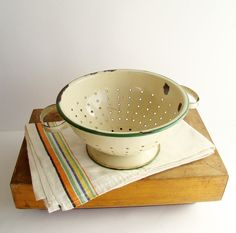 This worn old enamelware yellow and green colander is full of character and…