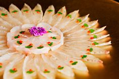 Tomo Restaurant usuzukuri for four; fluke sashimi, piece of cilantro, dot of hot sauce, served with ponzu jelly. Delish