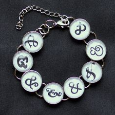 """I Love Ampersands & Typography  Glass Charm Bracelet by ScriptCharms  The """"I Love Ampersands"""" charm bracelet is the perfect gift for your favorite graphic designer, type designer, typophile or lover of fonts! If she has a Pinterest board devoted to typefaces, this is for her.  This beautiful silver plated metal and glass charm bracelet features eight charms, each with a beautiful ampersand, in a variety of typefaces."""