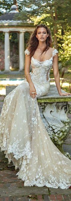 This romantic wedding dress has so much charm. From the lacy cap sleeves to the ivory tone of the underlay, the mermaid wedding dress shape emphasizes the drama of this dress and makes the sizable train a natural extension of the brides look.