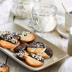 Kokosraspeln, gemahlene Mandeln und dunkle Schokolade werden ohne raffinierten Zucker zu leichten Knuspertalern für den Low-Carb-Weihnachtsteller.