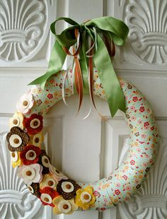 Felt Wreath Precious Wreath by thechicadeeshop on Etsy Overpriced and I'd use fabric to wrap the form in instead of paper strips but nice idea.