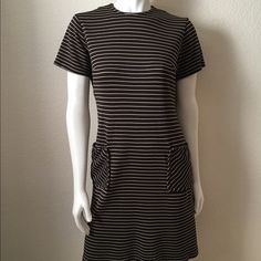 """Vintage 1960's Brown Striped Dress Vintage 1960's Brown Striped Dress comes in brown polyester with off white stripes, two front pockets, short sleeves with a back zipper closure. 100% Polyester. Size: (M) Bust: 36"""" Waist: 32"""" Hips: 38"""" Length: 35 1/2"""" Shoulder to Shoulder: 15"""". In excellent condition. Vintage Dresses Midi"""