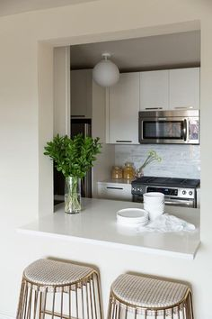 Chic kitchen boasts white cabinets paired with white quartz countertops and a linear marble tiled backsplash.
