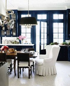 Vignette of a killer eat-in kitchen by Windsor Smith. Love the deep marine blue cabinets and french doors, marble countertops, crisp white mouldings and plaster ceiling detail (though it might be deeply embossed wallpaper), dark wood table, stainless steel appliances and hanging pot rack, black shaded light fixture, and glimmering white tile floor. Oh, and that skirted wingback.
